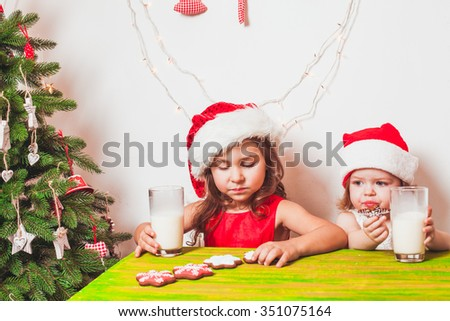 Two small Santas are drinking milk and eating colorful gingerbreads - stock photo