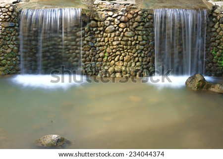 Two small waterfalls separated by a stone wall.  - stock photo