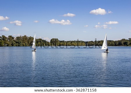 Two Small white boats sailing on the lake  - stock photo