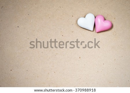 Two small wooden heart (white, pink) on rough paper background, decoration