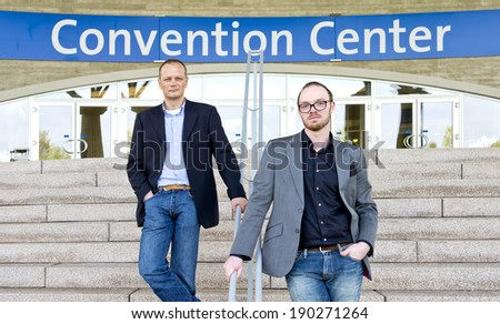 Two smart casual dressed colleagues, posing on the steps in front of a convention center - stock photo