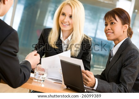 Two smart ladies listening to explanation of their boss with attention