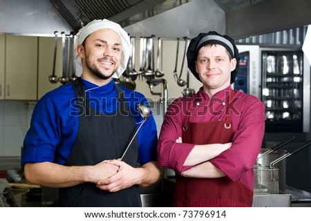 two smiley chefs in commercial kitchen - stock photo