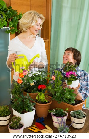 Two smiling aged women near table with many flowerpots