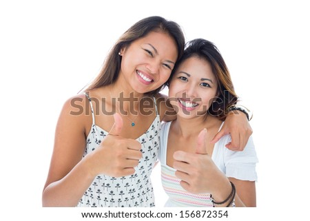 Two smiling asian women giving thumbs up on white background - stock photo
