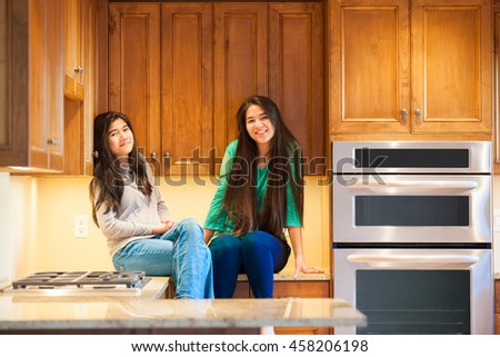 Two smiling biracial Asian Caucasian teen girls sitting on counter in modern kitchen, next to wall ovens - stock photo