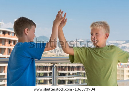 Two smiling boys in colored T-shirts are greet each other on the background of building under construction - stock photo