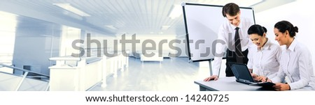 Two smiling business ladies sitting at table and looking at laptop monitor while their partner standing near by - stock photo