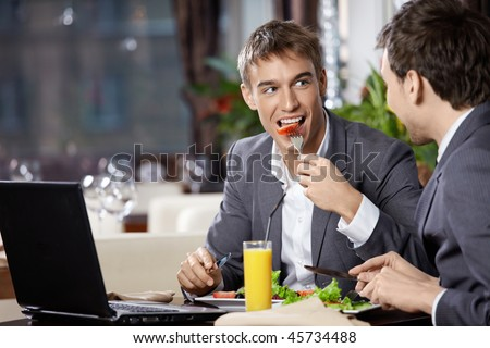 Two smiling business men eat at restaurant - stock photo