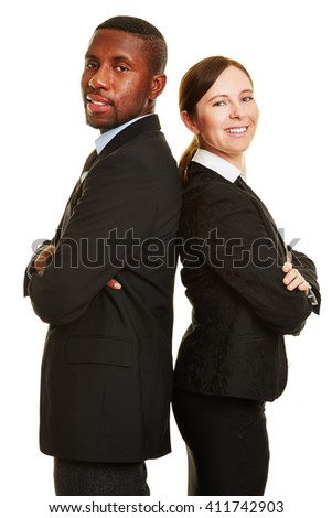 Two smiling business people leaning back on back