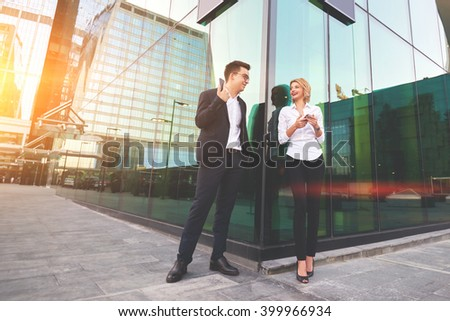 Two smiling business workers with mobile phone in hands are having pleasant conversation before their joint presentation. Cheerful man and woman skilled financiers is talking during break at job - stock photo