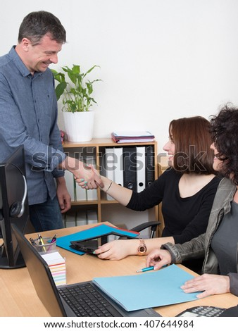 Two smiling businessman shaking hands in office