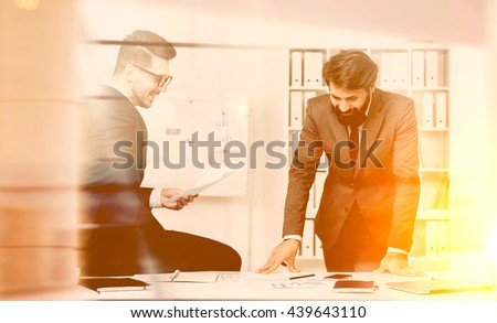 Two smiling businesspeople working together in modern office. Toned image - stock photo