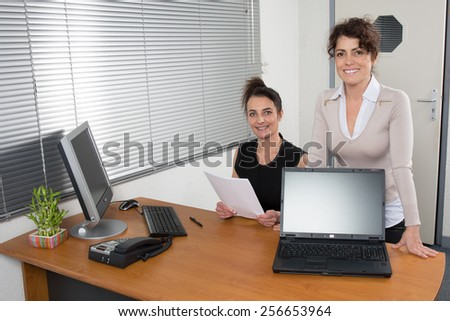 Two smiling businesswomen displaying their team project on a laptop