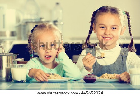 Two smiling cheerful girls eating healthy oatmeal at home kitchen - stock photo