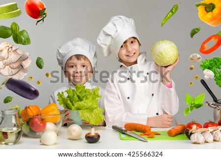 two smiling children-cooks by the table with flying vegetables in hands - stock photo