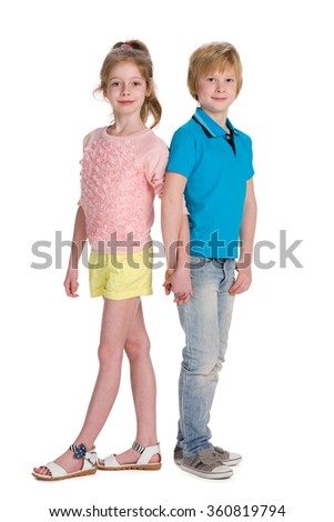 Two smiling children stand together on the white background
