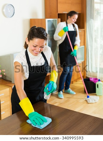 Two smiling cleaners cleaning room together