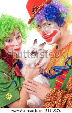 Two smiling clown with a white rabbit. Isolated - stock photo
