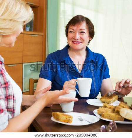 Two smiling colleagues in years drinking tea and talking during coffee break - stock photo