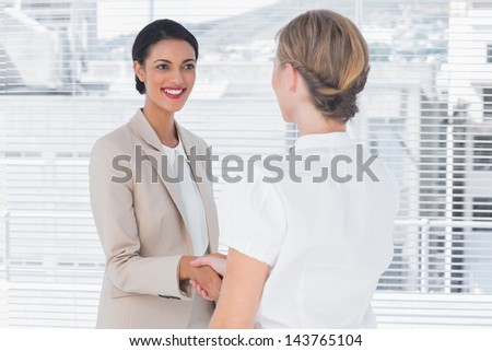 Two smiling colleagues shaking hands in office