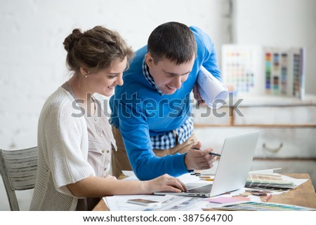 Two smiling colleagues working together, discussing ideas for new project at office desk in modern design agency. Young man pointing at screen. Attractive cheerful designer woman sitting using laptop
