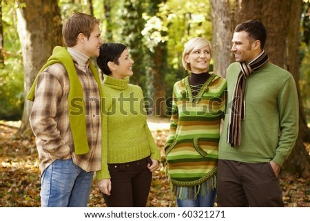 Two smiling couples talking in autumn forest.?