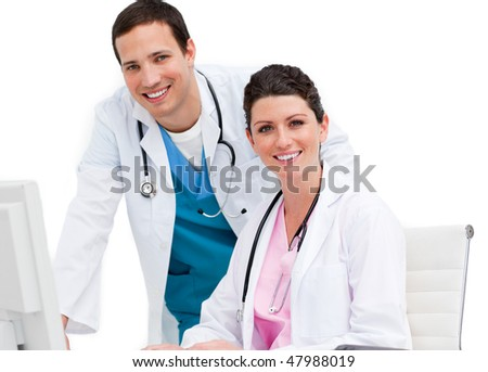 Two smiling doctors working at a computer against a white background - stock photo