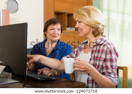 Two smiling elderly women looking at PC screen with cup of coffee in hands - stock photo