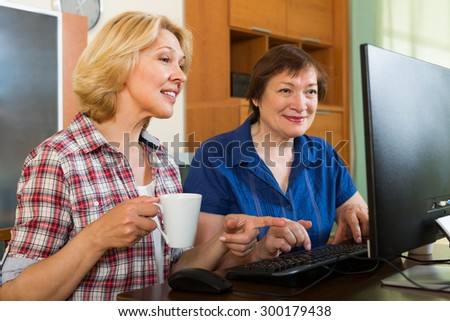 Two smiling elderly women looking at PC screen with cup of tea in hands - stock photo