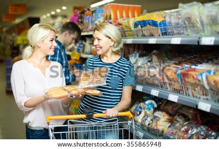 Two smiling female customers buying bread and pastry in food shop - stock photo