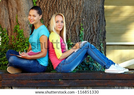two smiling female student sit on bench under an old tree - stock photo