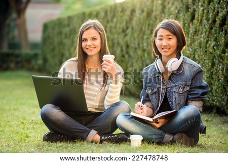 Two smiling female students are sitting on the grass at campus, with laptop. - stock photo