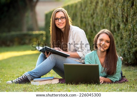 Two smiling female students are sitting on the grass with laptop at campus. They are looking at camera. - stock photo