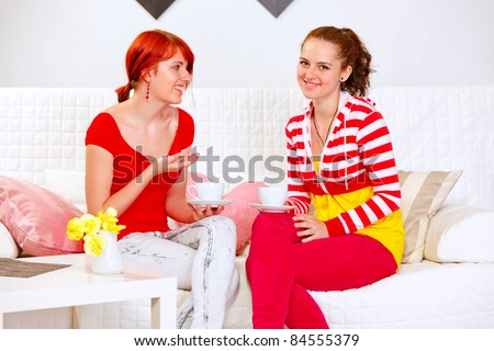 Two smiling girlfriends talking and drinking tea at home - stock photo
