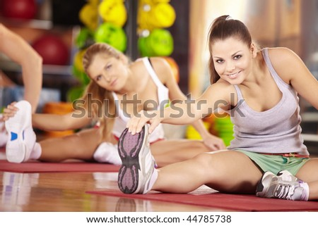 Two smiling girls do exercise in sports club