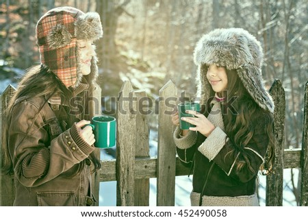 Two smiling girls drinking hot tea autumn day in the countryside. Cross process vintage soft focus. - stock photo