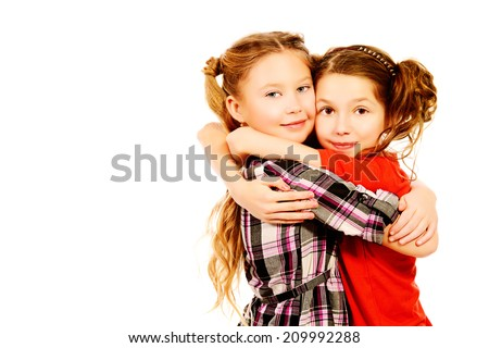 Two smiling girls embracing each other like best friends. Isolated over white. - stock photo