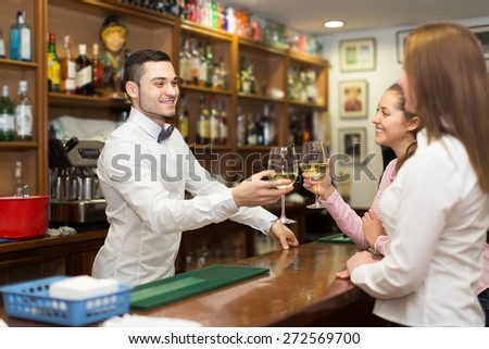 Two smiling girls flirting with young handsome barman at bar - stock photo