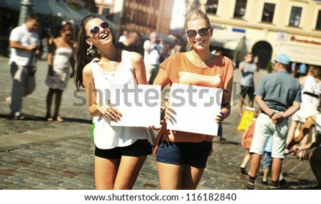 Two smiling girls holding empty board - stock photo