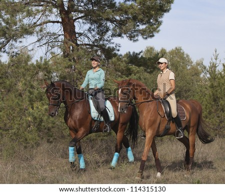 Two smiling girls horseback rides on a trail in the forest. - stock photo