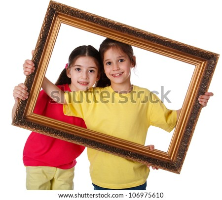 Two smiling girls looking through a vintage picture frame, isolated on white - stock photo
