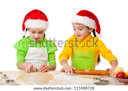 Two smiling girls roll out dough, christmas cooking. Isolated on white - stock photo