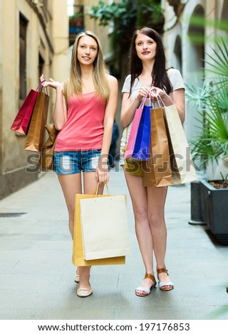 Two smiling girls walking with purchases in European city