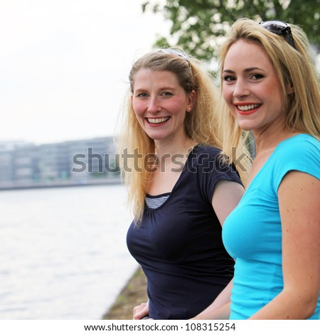 Two smiling happy women Two smiling happy women standing side by side overlooking a river as they enjoy an afternoon relaxing in each others company - stock photo