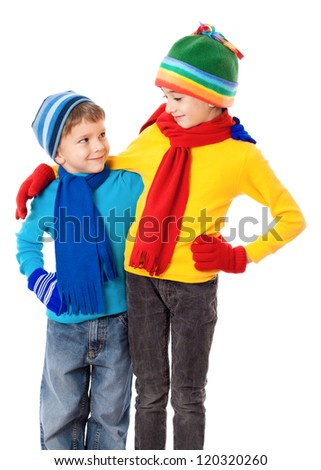 Two smiling kids in winter clothes standing together, isolated on white - stock photo