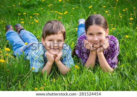 Two smiling kids lying together on green grass meadow - stock photo