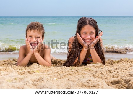 Two smiling kids on the beach lying down together near coastline