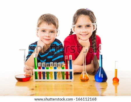 Two smiling kids on the desk with chemical equipment, isolated on white - stock photo