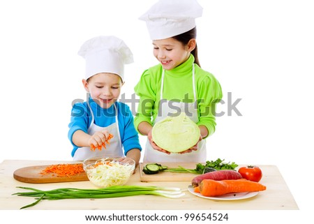 Two smiling kids preparing salad, isolated on white - stock photo